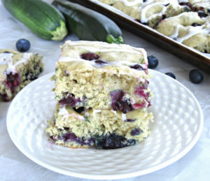 Easy dairy-free blueberry zucchini cake recipe with the lemon icing glaze. Bake it on the sheet pan to make cake bars. #dairyfree #sheetcake #zucchinicake #lemonicing for full recipe on craftyforhome.com